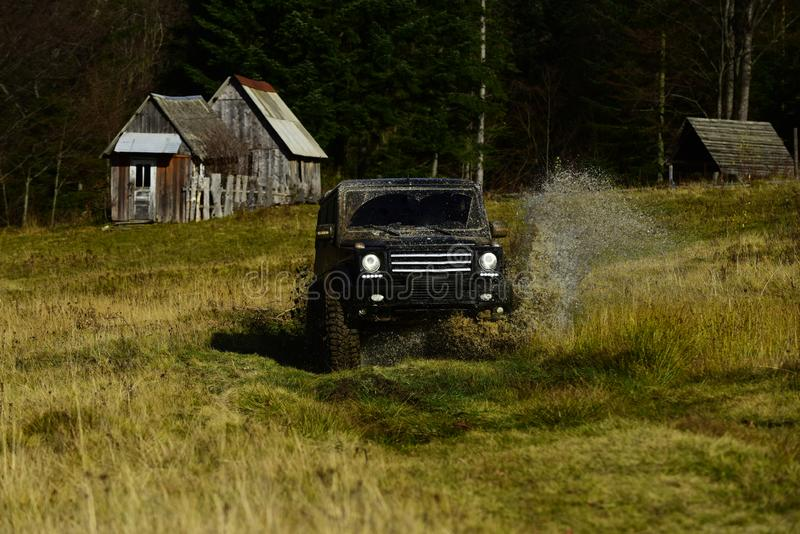 SUV crossing puddle and making splash. Extreme and four wheel drive concept. Off road car in black color takes part in stock photos