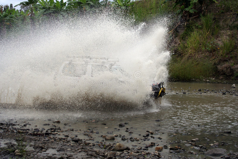 SUV crossing water at high speed stock photography