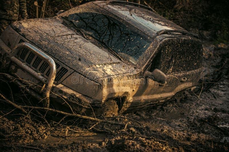 SUV cubrió con fango en la trayectoria con la rodera profunda imagen de archivo