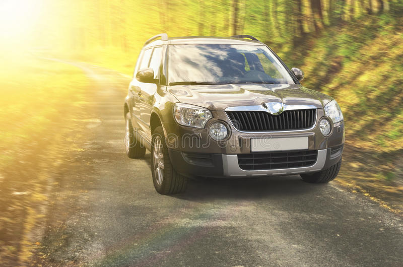 SUV on the road. Suv car on a road in the autumn forest lit by sunny beam royalty free stock images