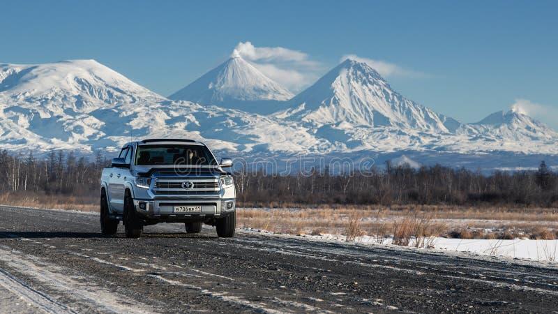 SUV japonais conduisant le long de la route sur le fond des volcans d'hiver le jour ensoleillé images stock