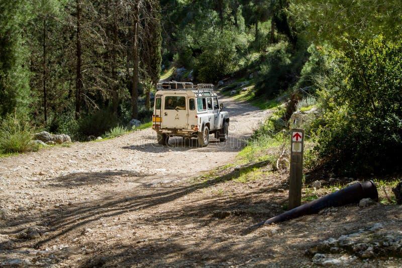 SUV monta en la carretera nacional en el bosque, Israel imagen de archivo libre de regalías