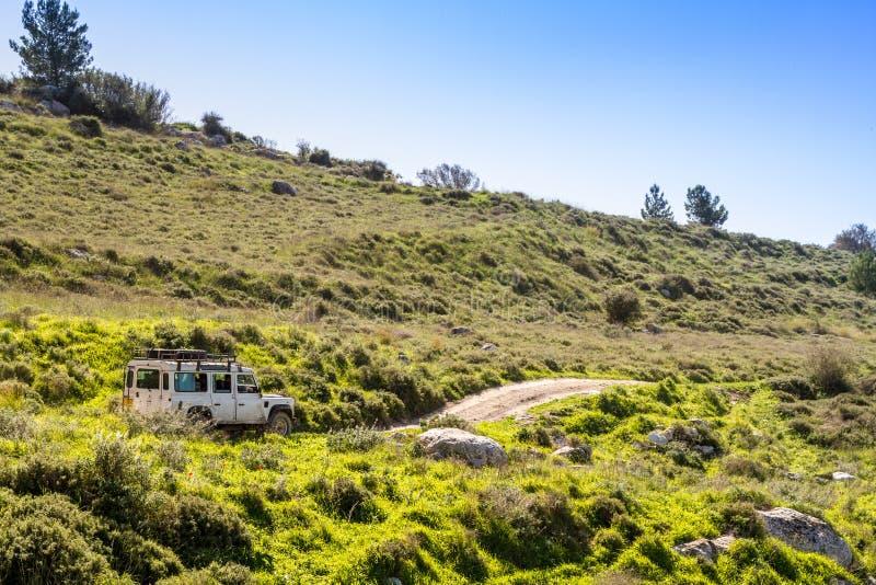 SUV monta en la carretera nacional entre las colinas y los prados, Israel fotografía de archivo