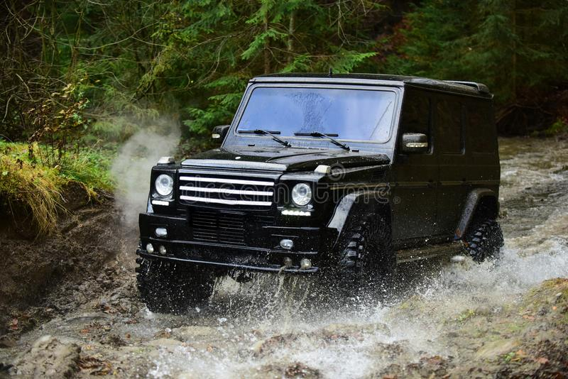SUV or offroad car in black color crossing water stream Car racing with creek on way. Offroad race in forest Extreme. SUV or offroad car in black color crossing royalty free stock photos