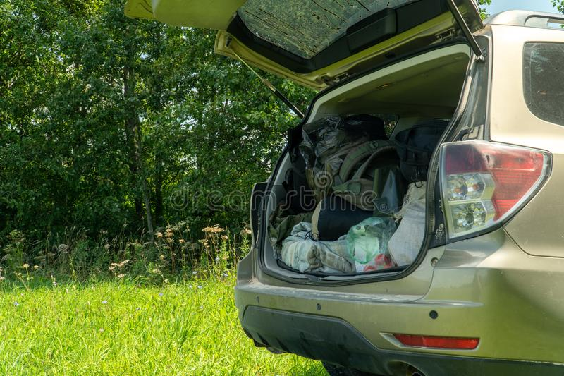 SUV with open boot packed full of camping equipment. Outdoors scenery.  stock photography