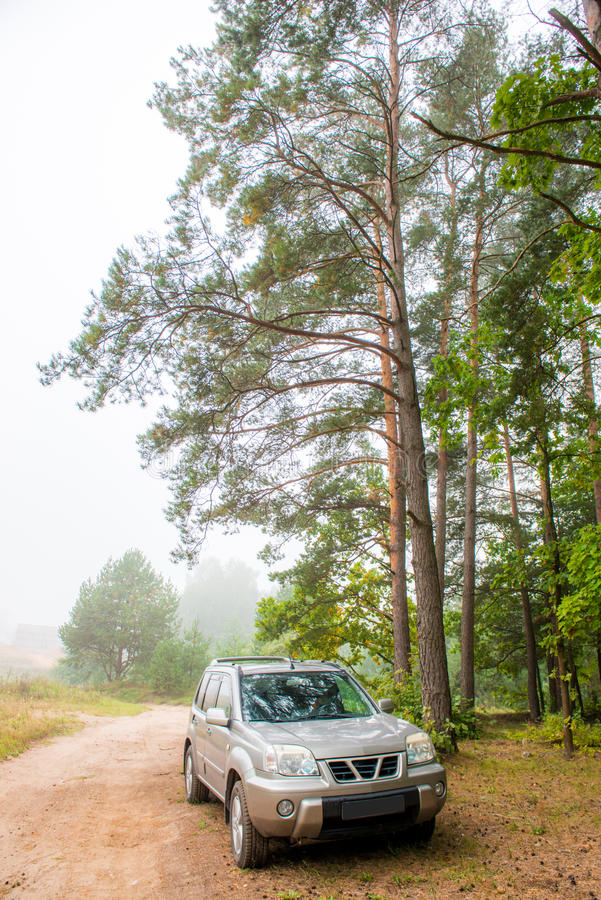 Suv parked at roadside. Misty forest and road, gloomy day. Car suv parked at roadside stock photography
