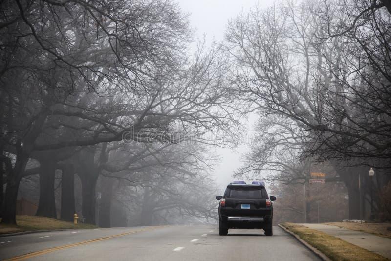 SUV que conduz sobre um monte na rua da cidade sob ramos pendendo sobre desencapados assustadores durante uma névoa pesada - sina fotografia de stock