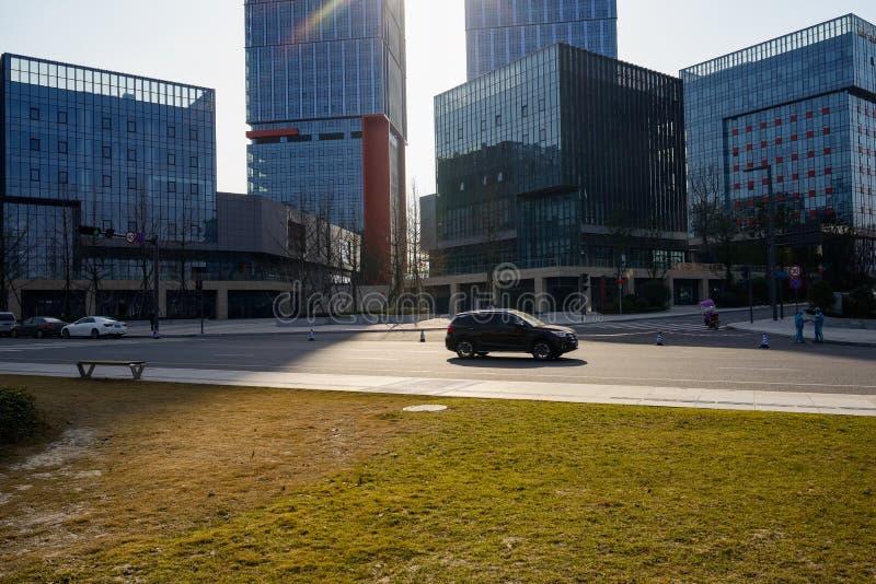 SUV que corre en el camino antes de edificios modernos en afte soleado del invierno fotografía de archivo libre de regalías