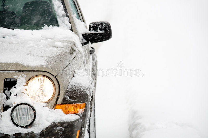 SUV in snow. SUV with four wheel drive in the snow, close up. Still snowing with very limited visibility, right side of frame unedited royalty free stock image