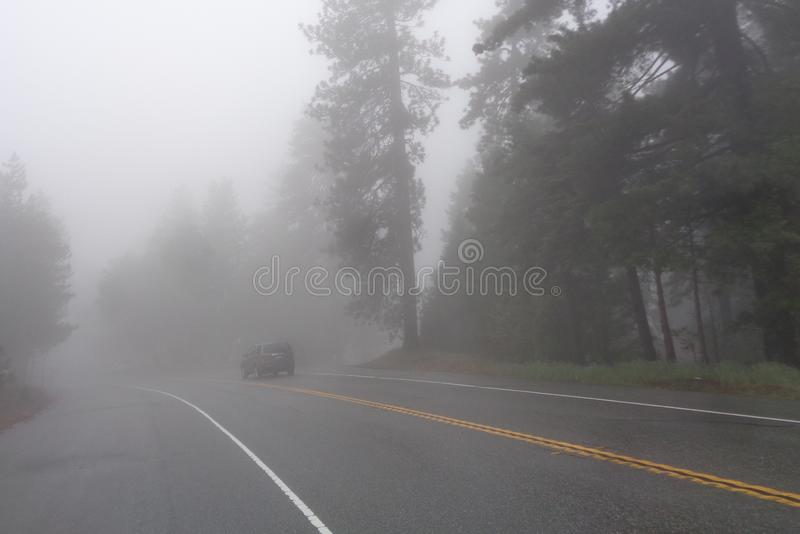 SUV traveling on Foggy Mountain Road. Image of a dark grey vehicle driving on a wet mountain highway away into thick mountain fog on a cold spring afternoon stock photography