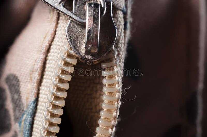 Suwaczka przepięcie z kędziorkiem na torba beżowym kolorze, zbliżenie zdjęcia royalty free