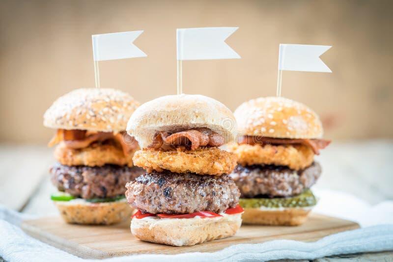 Suwaki wzmacniają wysokich minych hamburgery dzieli jedzenie obrazy stock