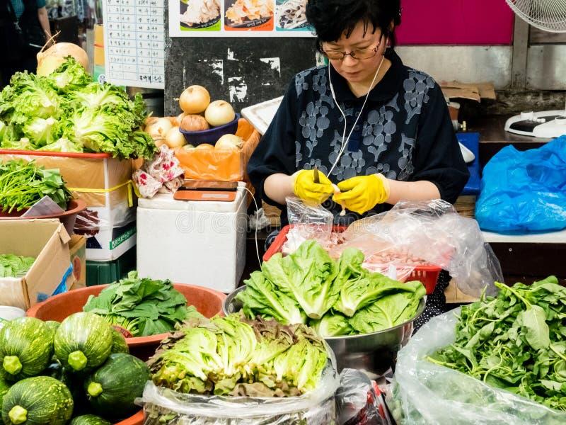 Suwon, korea południowa - Czerwiec 26, 2017: Sprzedawca kobieta struga czosnku dla sprzedaży w ulicznym rynku przy śródmieściem w zdjęcie royalty free