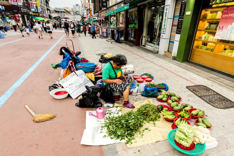 Suwon, S?dkorea - 25. Juni 2017: Verk?uferfrau, die Gem?se und Fr?chte im Stra?enmarkt am Stadtzentrum in Suwon verkauft lizenzfreie stockfotos