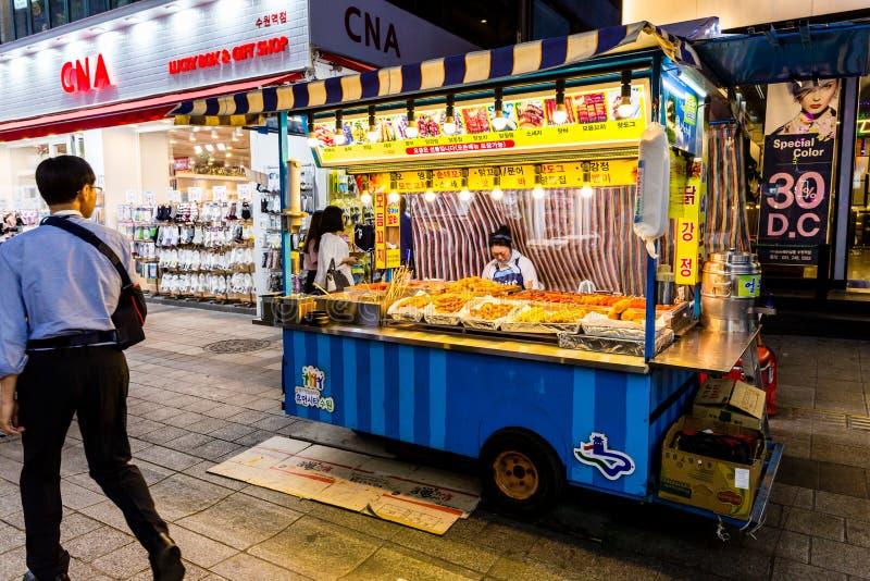 Suwon Sydkorea - Juni 14, 2017: Vänta för kvinnasäljare av köpare i hennes snabbmatkiosk på den huvudsakliga gatan i Suwon arkivfoton
