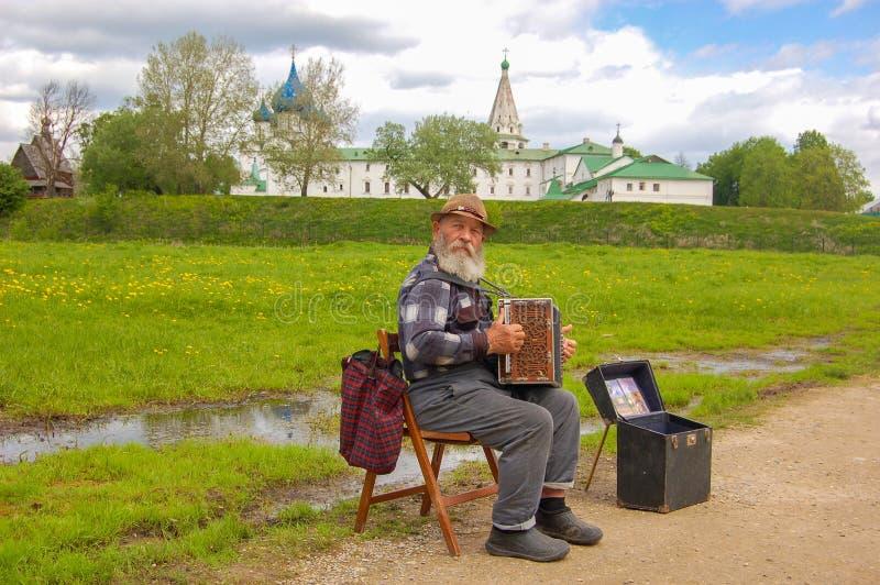 suzdal russia 28 Maj 2017 Gatamusiker, gammal farfar med hans dragspel på bakgrunden av Kreml av Suzdal royaltyfri fotografi
