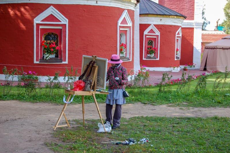 Suzdal, Russland 16. August 2015 Ein Straßenkünstler in der alten Stadt zeichnet von der Kirche stockfoto