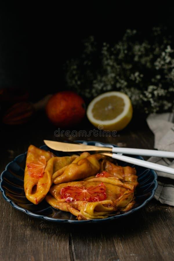 Suzette francês tradicional dos crepes com as laranjas ensanguentados vermelhas, panquecas do blini do russo - refeição do festiv fotografia de stock royalty free
