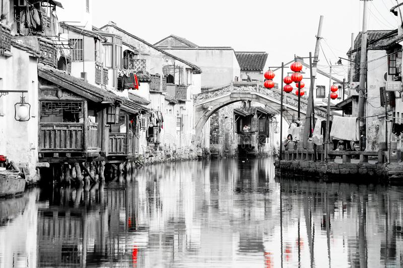 Suzhou, ancient chinese canal, old houses, lanterns, wooden boats and ancient bridge near Shanghai, China. Black, white, red image royalty free stock images