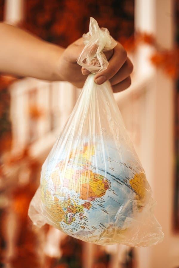 Svälld planet Jorden och en hand på gatan Jorden kvävs och kvävs av plast royaltyfria bilder