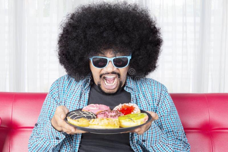 Svälta mannen som rymmer en platta av läckra donuts arkivbild
