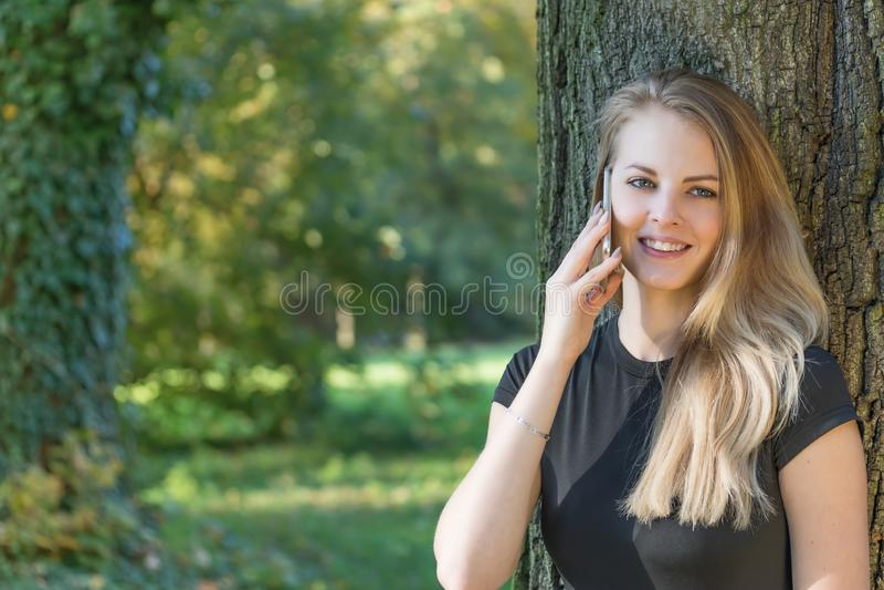 Sväng attraktiv ung flicka ringer i parken royaltyfria foton