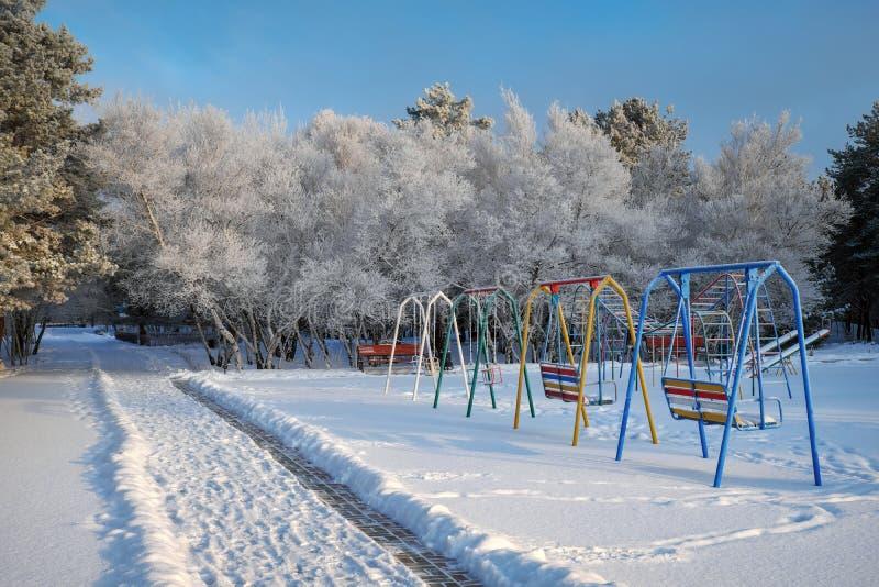 Svänga på lekplatsen som täckas med insnöad vintertid royaltyfria bilder