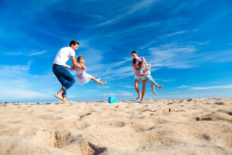 Svängande barn för förälder på stranden arkivfoton