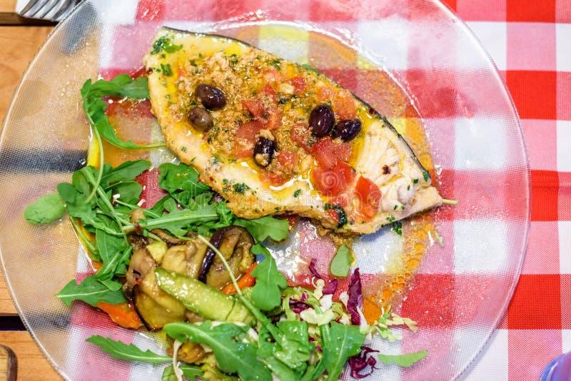 Svärdfiskinsats med olivolja och grönsaker arkivfoto