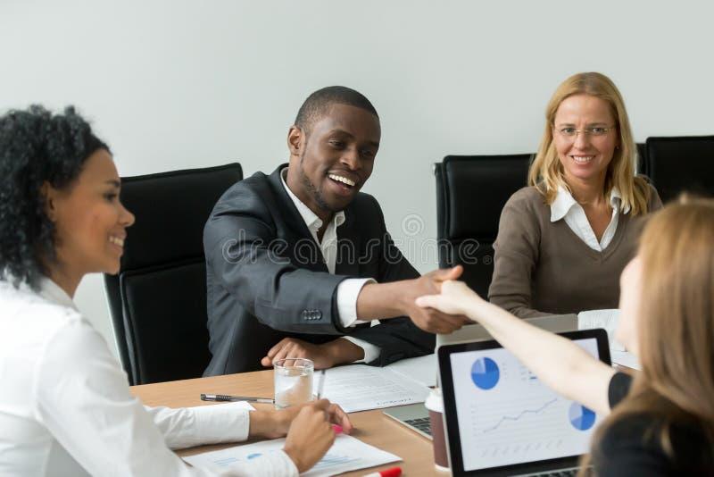 Svärta den tillfredsställda nya kvinnliga vita partnern för affärsmanhandshaking royaltyfri foto