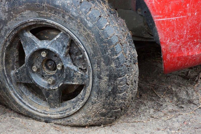 Svärta det plana gummihjulet av en röd bil på en grusväg arkivbilder