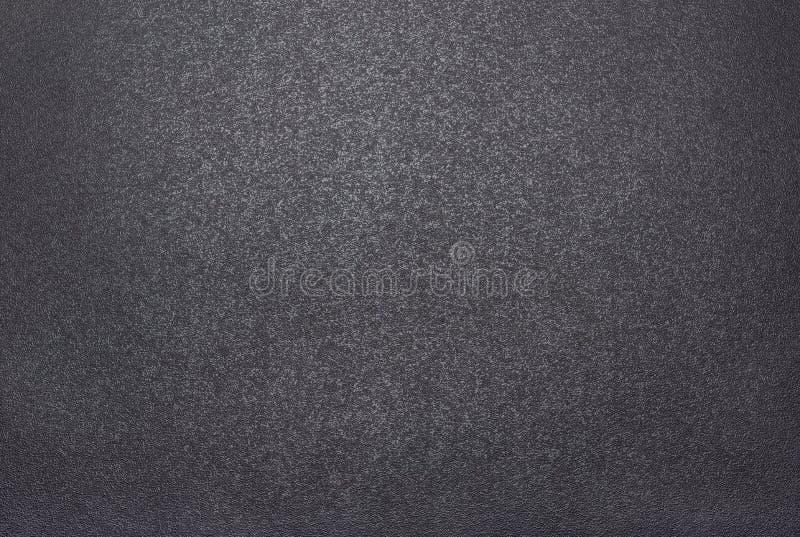 Svärta grov texturerad bakgrund som tänds med dunkelt ljus arkivfoto
