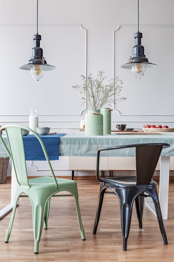 Svärta och göra grön stol på tabellen i modern matsalinre med lampor och blommor Verkligt foto royaltyfria foton