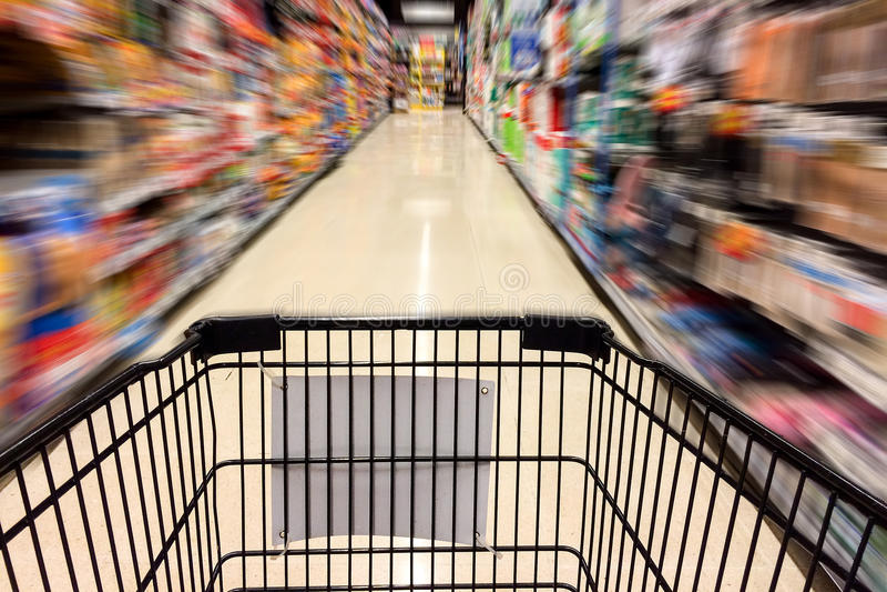 Svärta shoppingvagnen med suddig bild för rörelse av shopping i supermarket, shoppa Time för julferiebegrepp royaltyfri fotografi