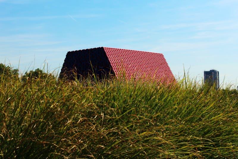 Sväva plast- pyramidinstallation av konstnären Christo på det slingrande i Hyde Park som ses bak gräsblad arkivbild