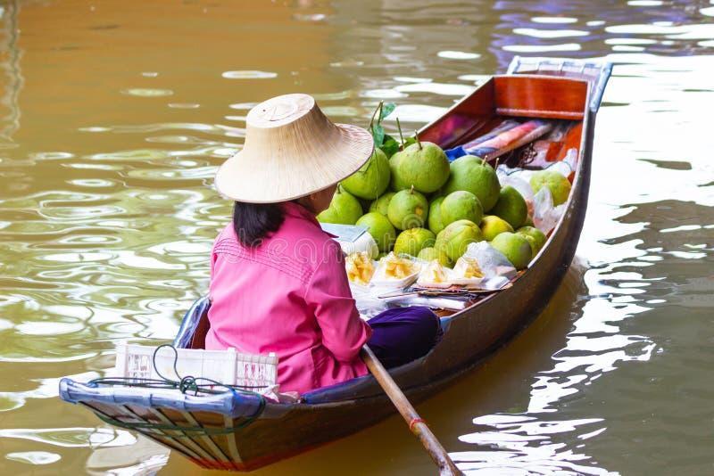 Sväva små fartyg för marknad, Thailand laden med färgglade frukter och grönsaker och som paddlas av thailändska kvinnor arkivbilder