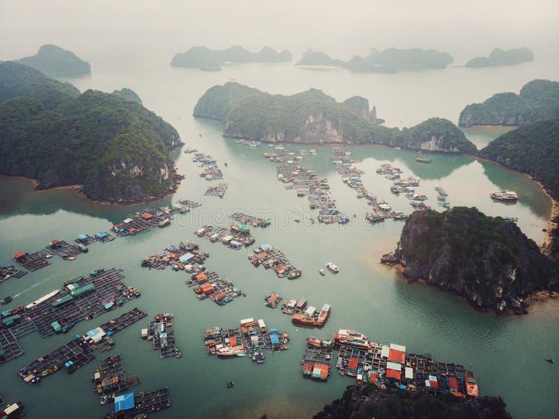 sv?va fiskaren  ?s-byn i l?ng fj?rd f?r mummel, nordliga Vietnam B?sta sikt, flyg- sikt arkivbild
