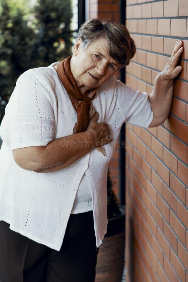 Svag farmor med att vänta för hjärtinfarkt royaltyfri bild