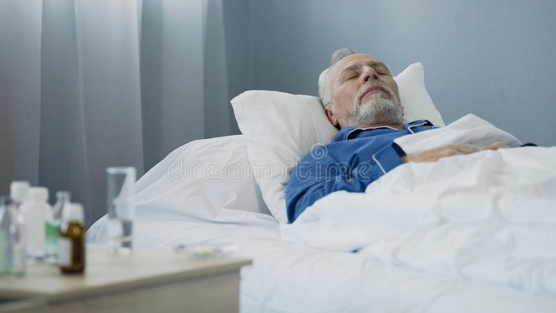 Svag manlig patient som ta sig en tupplur på sjukhussäng, når att ha tagit den dagliga dosen av läkarbehandlingen arkivbilder