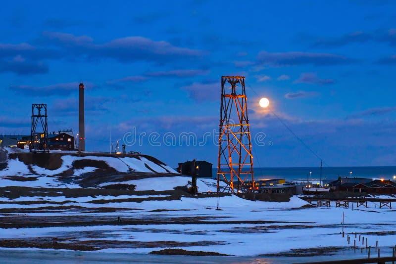 Svalbard - Longyearbyen - måne bak coalminingstolpar royaltyfri fotografi