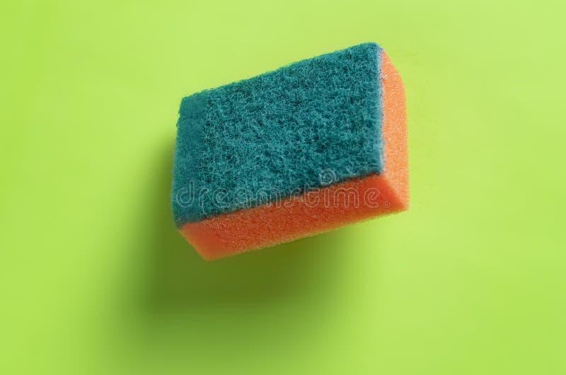 Svamp för tvättande disk som isoleras på färgrik bakgrund b royaltyfri bild