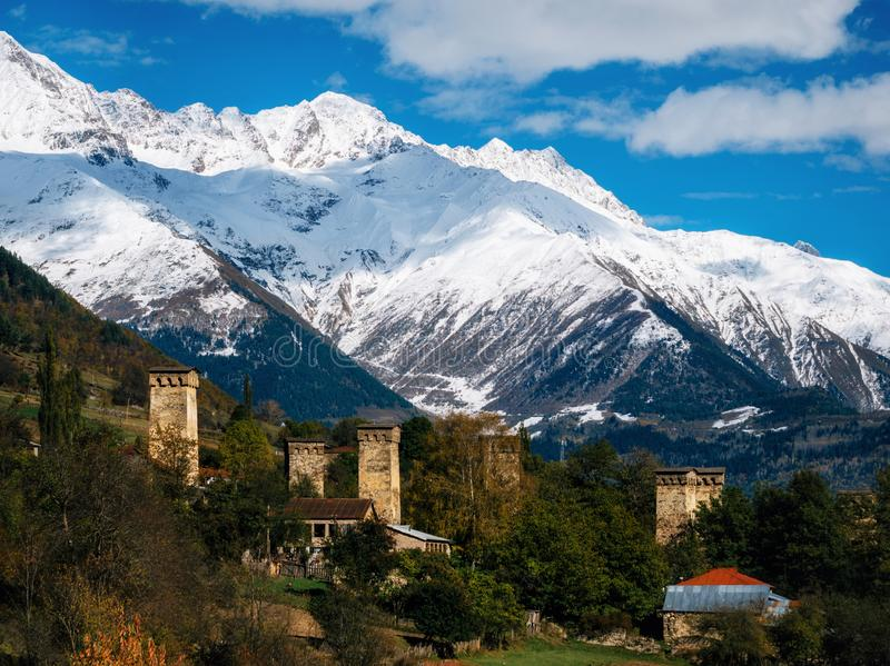 Svan towers in Mestia against mountains, Svaneti, Georgia. View of the Svanetian towers in Mestia village against mountains with glaciers snow peaks. Upper stock photos