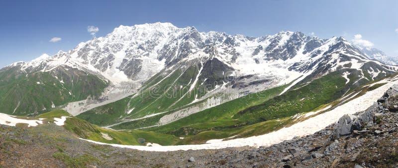 Svaneti山风景在乔治亚 与多雪的山峰的白种人土坎和绿草在明亮的晴朗的夏日 库存图片