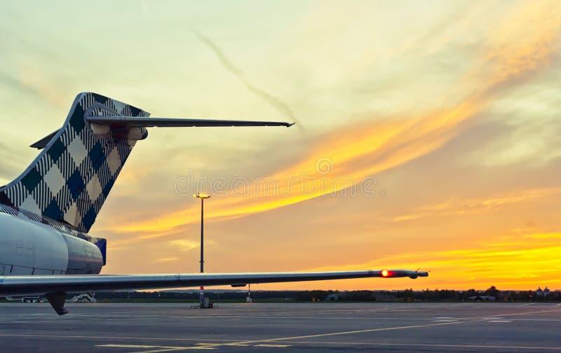 Svansen av ett flygplan på en solnedgångbakgrund royaltyfria bilder