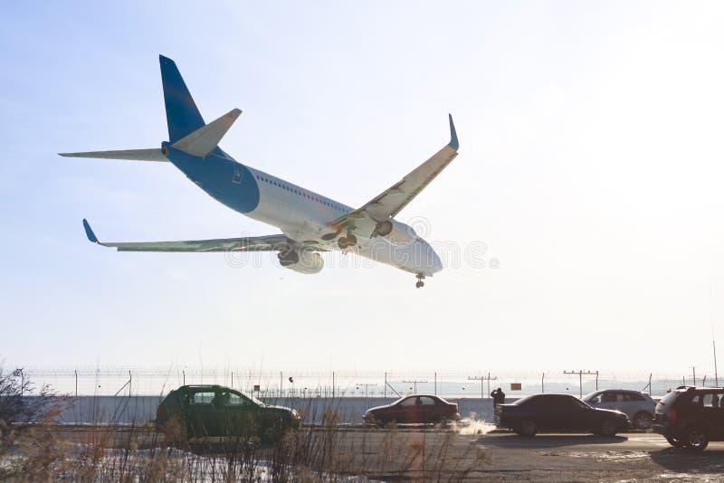 Svanssikt av landningflygplanet Flygplan som flyger över huvudvägen Väg med hög trafik nära flygplatslandningsbana Compar typ av  royaltyfri foto
