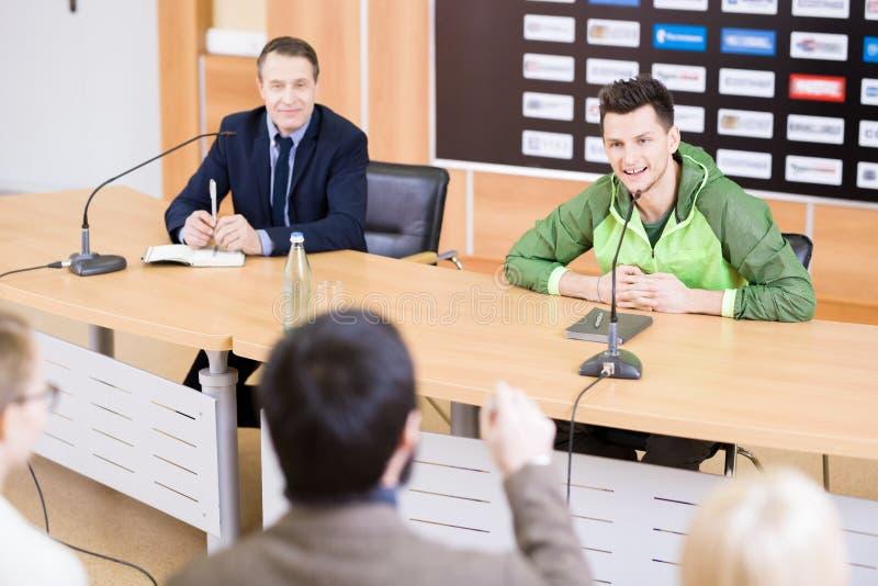 Svarande frågor för idrottsman på presskonferensen arkivbilder