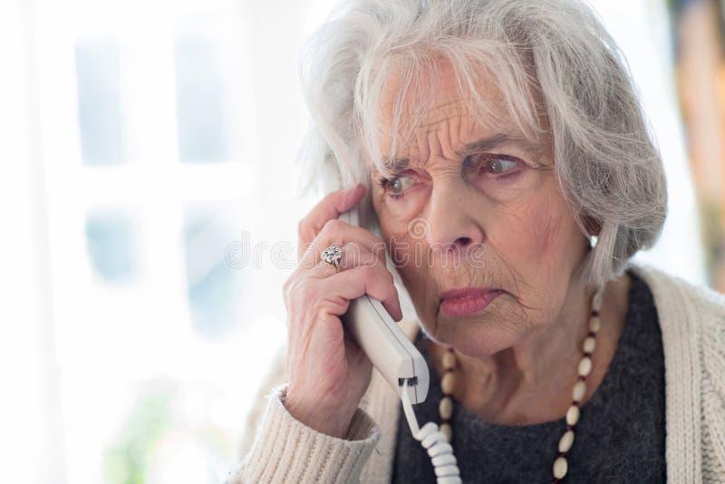 Svarande telefon för bekymrad hög kvinna hemma royaltyfri fotografi