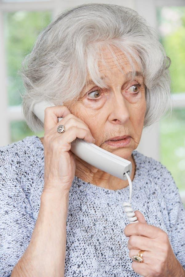 Svarande telefon för bekymrad hög kvinna hemma royaltyfri foto