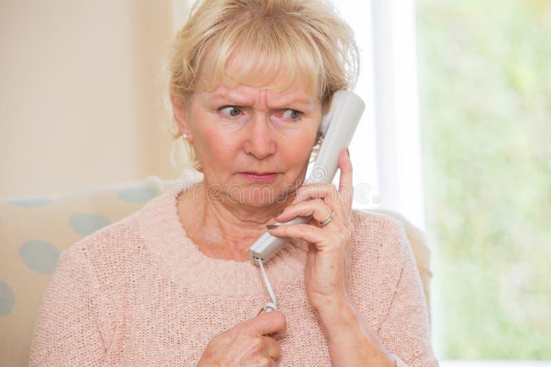 Svarande telefon för bekymrad hög kvinna hemma royaltyfria bilder