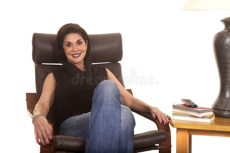 Svartöverkanten för äldre kvinna sitter stolleende arkivbild